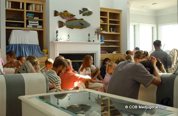 community praying with the visionary marija in the beach house